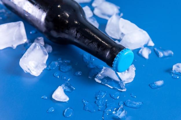 파란색 표면에 맥주 병 및 얼음의 근접 촬영 샷