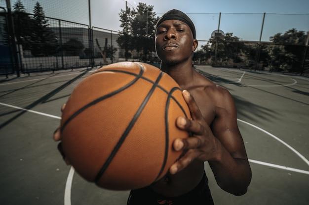 야외 안뜰에 있는 흑인 농구 선수의 클로즈업 샷
