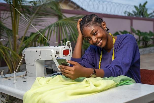 彼女の前に布で彼女の携帯電話に微笑んでいる黒人女性のクローズアップショット