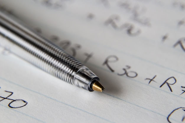 いくつかの数字とコードが書かれた紙に黒いペンのクローズアップショット