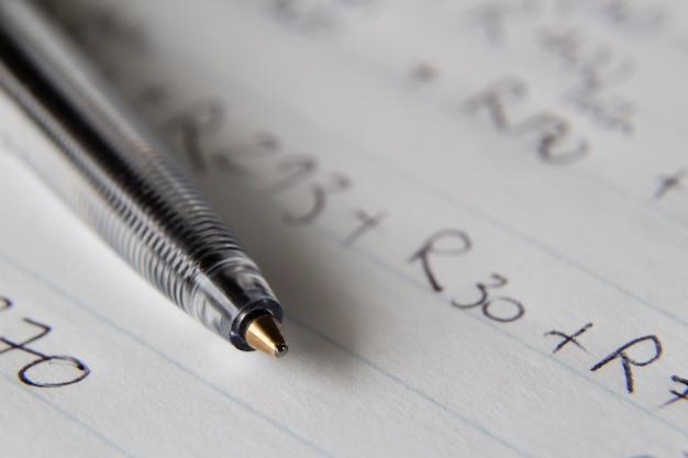 일부 숫자와 코드가 적힌 종이에 검은 펜의 근접 촬영 샷
