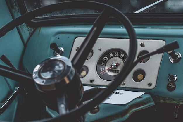 Съемка крупного плана черного рулевого колеса внутри голубого автомобиля