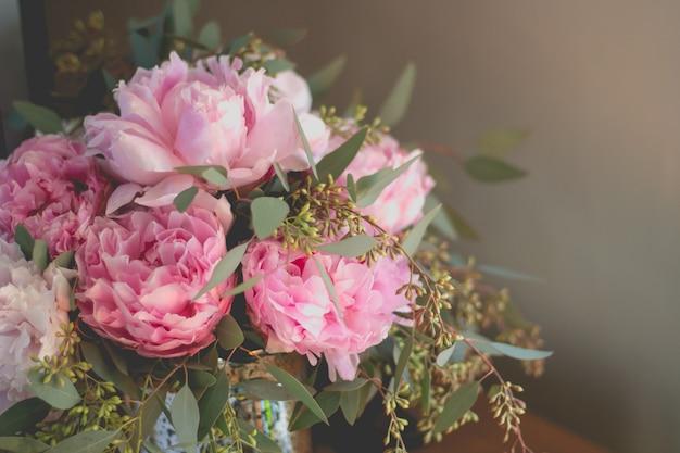 Макрофотография выстрел из букета розовых роз и других цветов с зелеными листьями