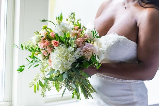 花の花束を保持している白いドレスを着た花嫁のクローズアップショット