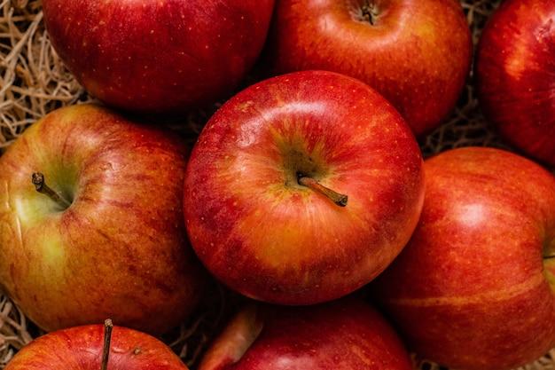干し草の表面にある美味しそうな赤いリンゴの束のクローズアップショット