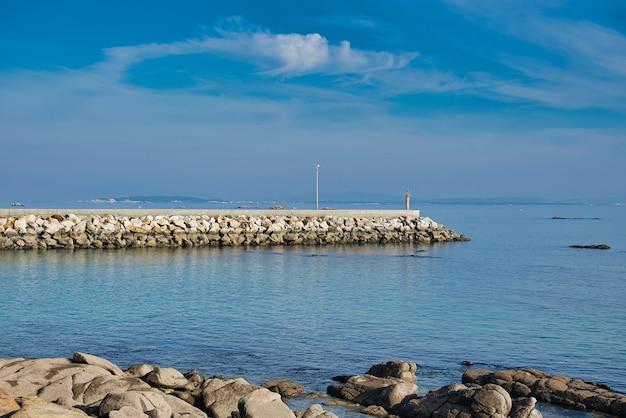 전경에 잔잔한 푸른 바다와 흰 바위의 근접 촬영