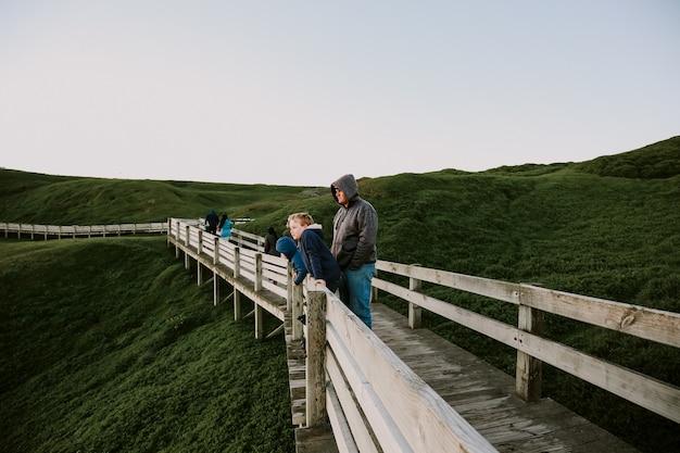 山の頂上を通る木製の小道を渡る白人の父と少年のクローズアップショット