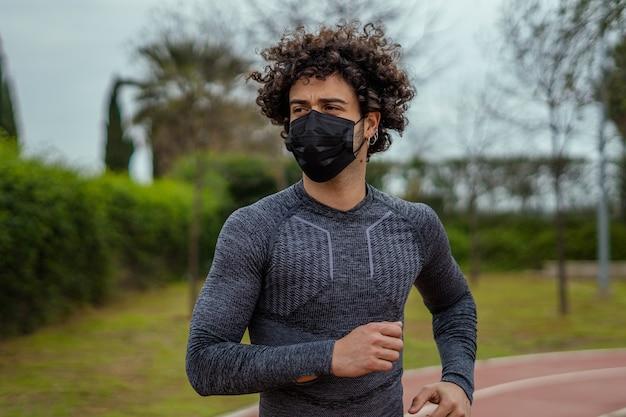 마스크를 쓰고 공원에서 달리는 백인 젊은 남성의 근접 촬영