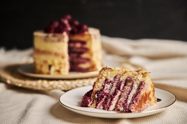 白いプレート上の桜のケーキのスライスのクローズアップショット
