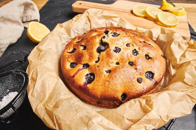 Крупным планом снимок вишневого торта с сахарной пудрой и ингредиентами сбоку на черном