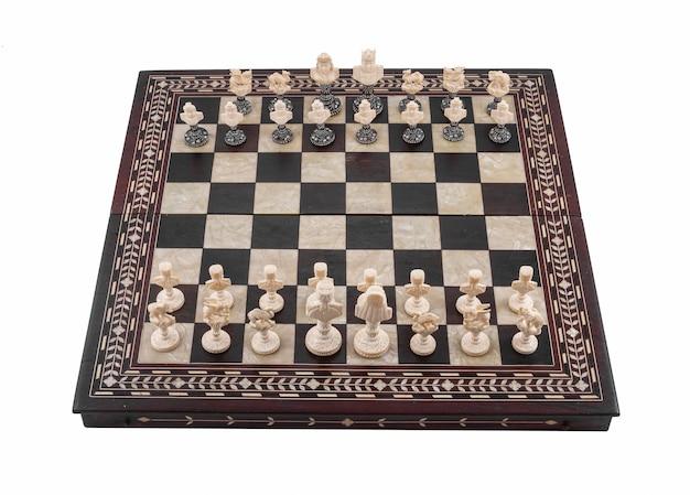 白で隔離されるチェスの木片とチェス盤のクローズアップショット