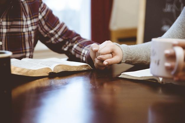 彼らの本を読んで白いテーブルの上に手をつないでカップルのクローズアップショット