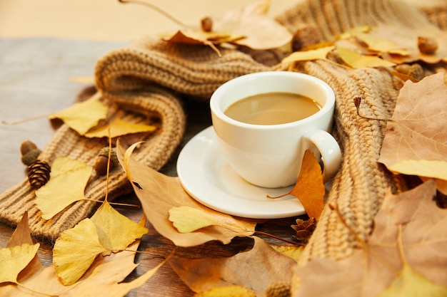 一杯のコーヒーと木の表面の紅葉のクローズアップショット