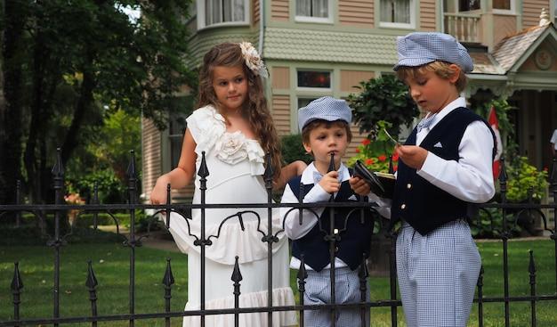 Снимок крупным планом симпатичной маленькой девочки и двух мальчиков в одинаковых костюмах, стоящих за забором