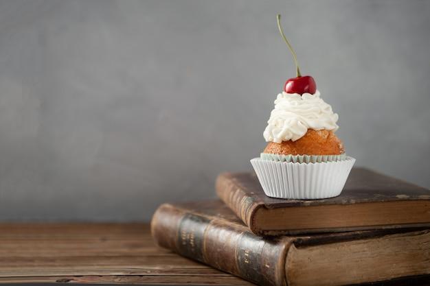 Снимок вкусного кекса со сливками и вишней сверху на книгах крупным планом