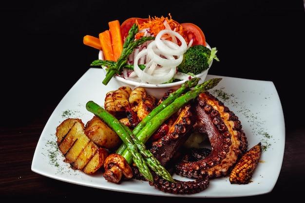Съемка крупного плана очень вкусного зажаренного в духовке блюда осьминога с зажаренной спаржей и овощами