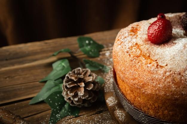 딸기, 소나무 콘, 테이블에 레드 베리와 함께 맛있는 스폰지 케이크의 근접 촬영 샷