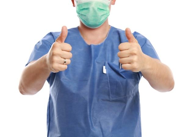 白い壁に分離された親指を持ち上げて医師のクローズアップショット