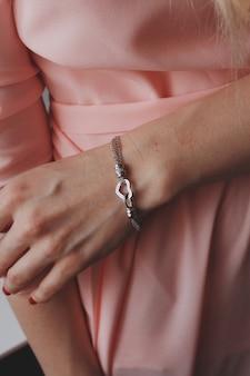 하트 펜던트와 함께 아름다운 은색 팔찌를 착용하는 핑크색 드레스를 입은 여성의 근접 촬영 샷