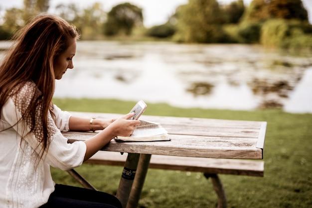 彼女のスマートフォンを使用しながら公園で座っている女性のクローズアップショット