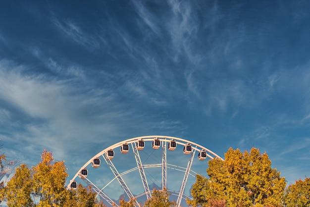 Крупным планом снимок колеса обозрения возле деревьев под голубым облачным небом