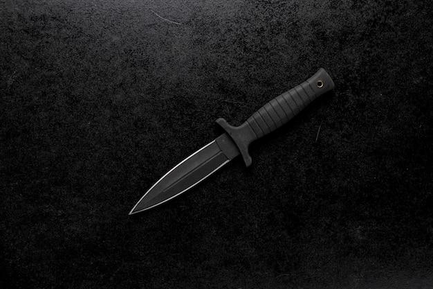 Снимок фиксированного острого ножа крупным планом на черном фоне