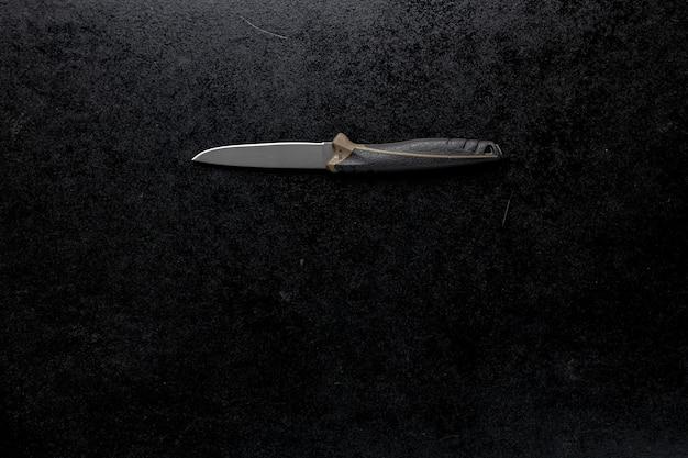 黒いテーブルに固定された鋭いナイフのクローズアップショット
