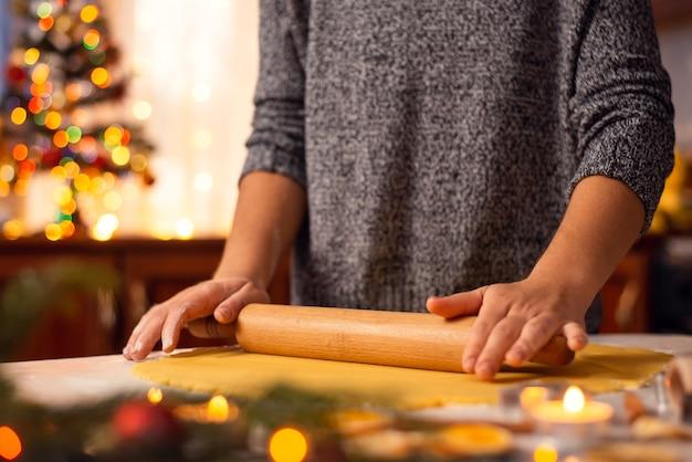 롤링 핀 베이킹 맛있는 크리스마스 비스킷의 도움으로 반죽을 평평하게하는 소녀의 근접 촬영 샷