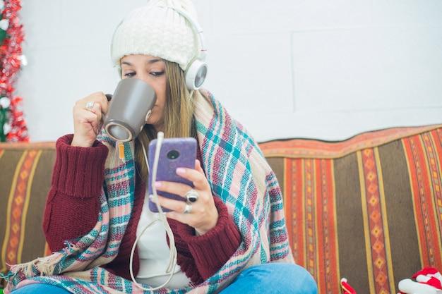 Снимок крупным планом девушки в наушниках, прикрытой шарфом, пьющей из кружки