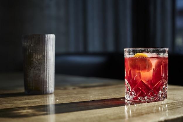 Крупным планом выстрел из бокала коктейля на деревянном столе