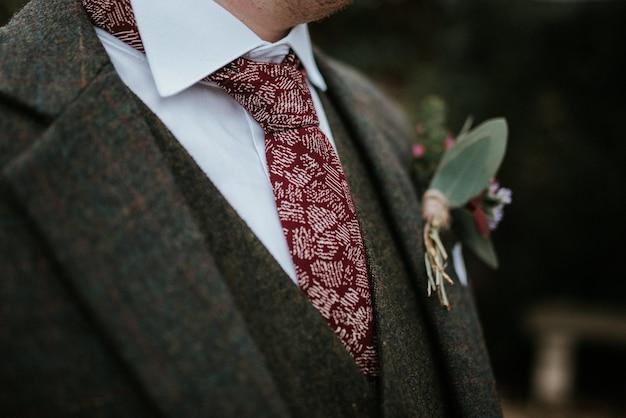 배경에 나무와 꽃과 붉은 무늬 넥타이와 신랑의 양복의 근접 촬영 샷