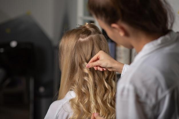 ヘアスタイリング中に美しいクライアントのカールに触れる美容師の手のクローズアップショット