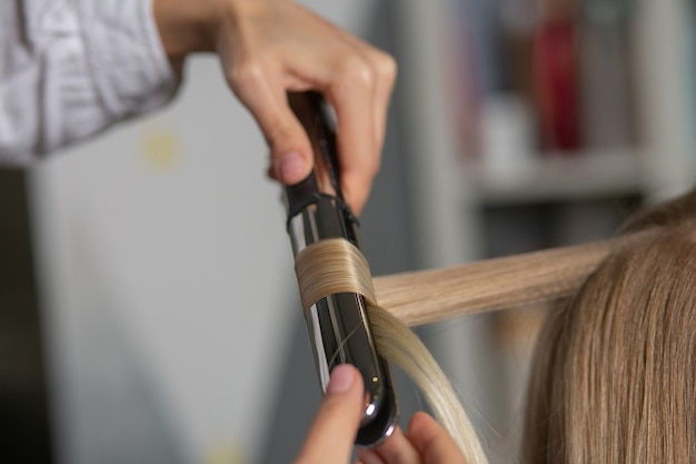 Крупным планом снимок парикмахера, делающего кудри с утюжком для укладки, блондинке в парикмахерской