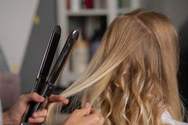 Крупным планом снимок парикмахера, делающего кудри с утюжком для укладки, клиенту в парикмахерской