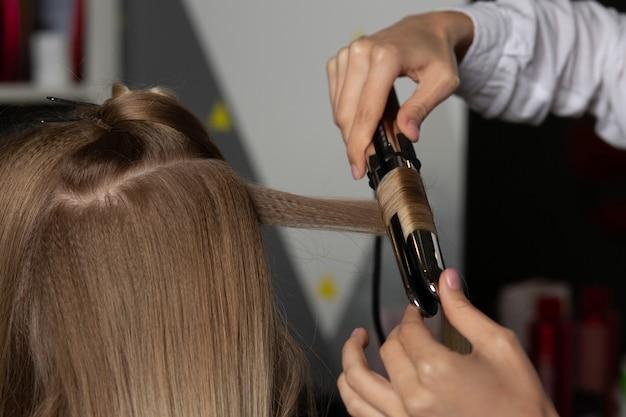 Крупным планом снимок парикмахера, делающего кудри утюжком для укладки, женщине с пышными светлыми волосами