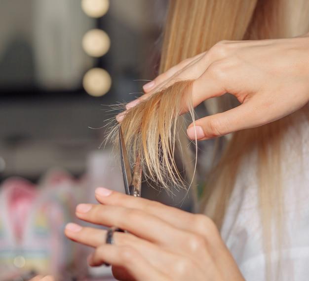 死んだ後のクライアントの髪を切る美容師の手のクローズアップショット