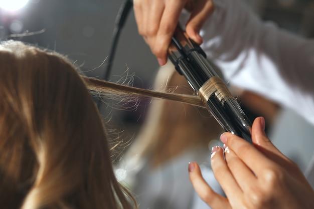 Крупным планом выстрелил парикмахер, работающий с белокурой женщиной в парикмахерской. создание красивых локонов плойкой