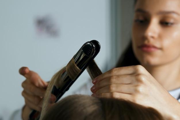 Крупным планом выстрелил парикмахер, работающий с белокурой женщиной в парикмахерской. создание ультрамодных локонов плойкой