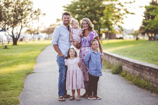 港の近くの芝生の上に立っている幸せな家族のクローズアップショット-家族の概念