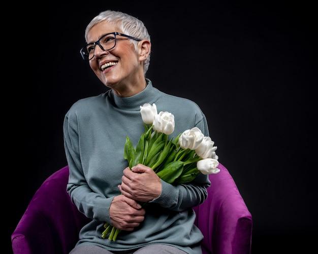 Снимок крупным планом счастливой женщины, держащей букет цветов - концепция женского дня