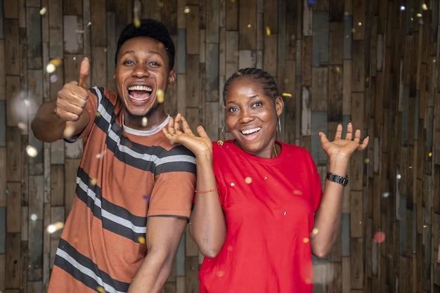Снимок крупным планом счастливого молодого мужчины и женщины, празднующей