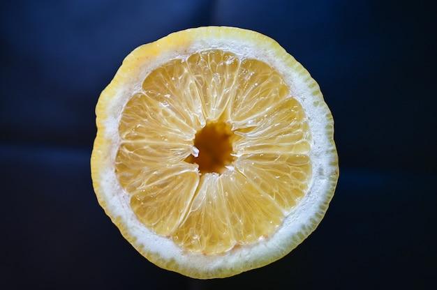 青で分離されたジューシーなレモンのクローズアップショット