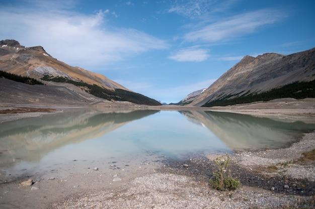 岩だらけの丘に囲まれた湖のクローズアップショット