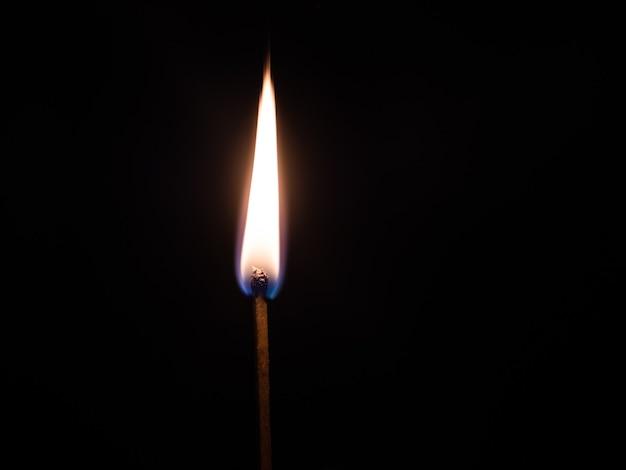 Снимок крупным планом зажженной спичечной палочки на черном фоне