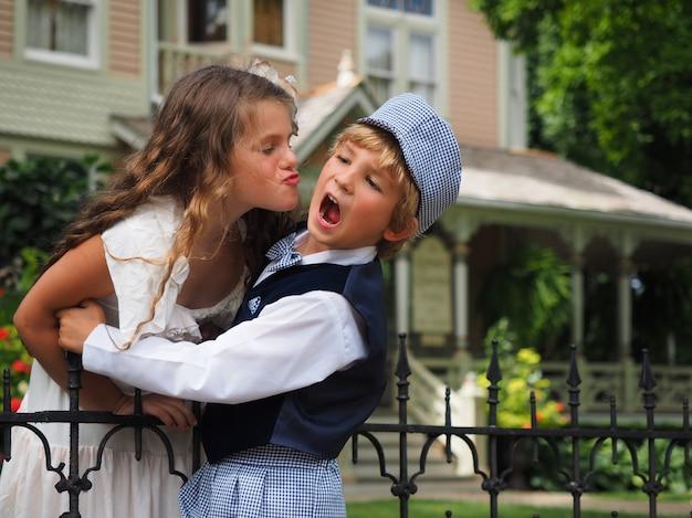 叫んでいる少年にキスをしようとしている小さな女の子のクローズアップショット