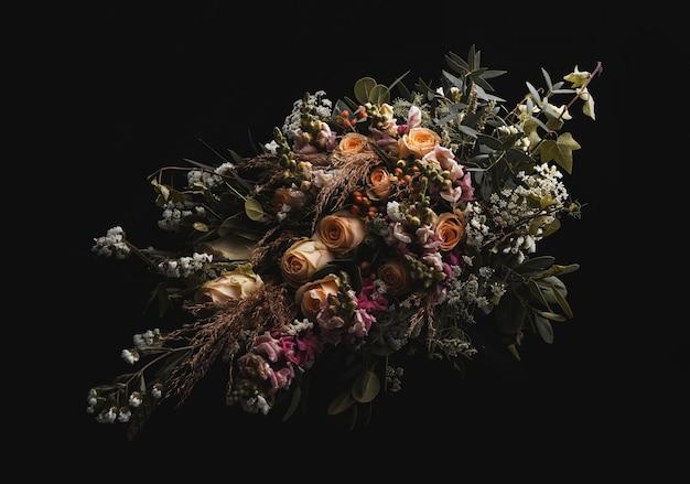 Снимок крупным планом роскошного букета оранжевых и коричневых роз на черном