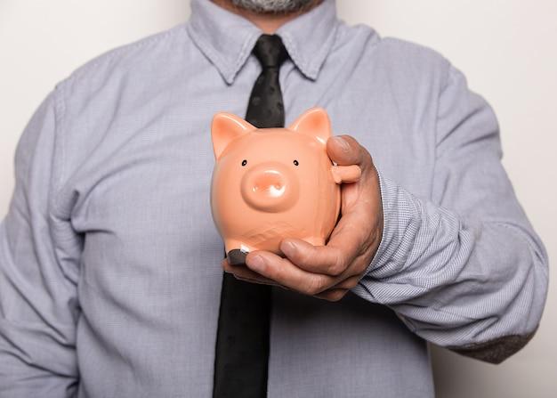 貯金箱を持っている男性のクローズアップショット