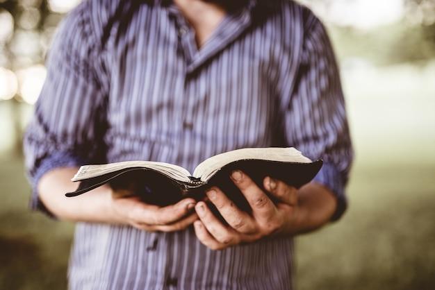 ぼやけた背景と開いた聖書を保持している男性のクローズアップショット