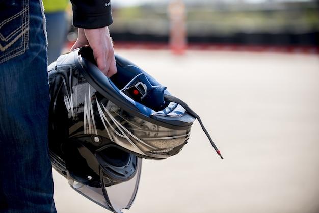 ぼやけた距離で彼のオートバイのヘルメットを保持している男性のクローズアップショット
