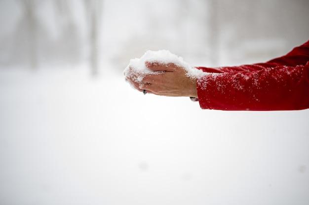 彼の手のひらで雪を保持している男性のクローズアップショット